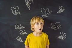 Le garçon est mordu par des moustiques sur un fond foncé Sur le tableau noir avec les moustiques peints par craie photos libres de droits