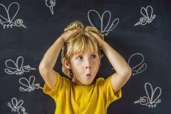 Le garçon est mordu par des moustiques sur un fond foncé Sur le tableau noir avec les moustiques peints par craie images libres de droits