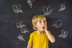 Le garçon est mordu par des moustiques sur un fond foncé Sur le tableau noir avec les moustiques peints par craie image stock