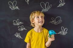 Le garçon est mordu par des moustiques tenant un fumigator sur un fond foncé Sur le tableau noir avec la craie peinte photos stock
