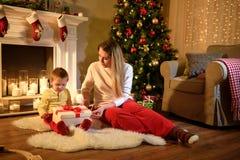 Le garçon est prêt à ouvrir son cadeau de Noël image stock