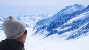 Le garçon est sur le dessus de Jungfrau de l'Europe avec le fond de montagne de neige photographie stock libre de droits