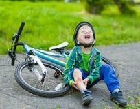 Le garçon est tombé du vélo en parc photographie stock