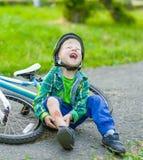 Le garçon est tombé du vélo en parc photos stock