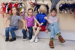 Le garçon et deux filles s'asseyant ainsi que des mannequins Photographie stock