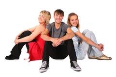 Le garçon et deux filles s'assied sur l'étage Image libre de droits