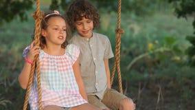Le garçon et la fille affectueux montent sur une oscillation se reposant l'un à côté de l'autre Le garçon embrasse la fille, elle clips vidéos