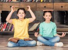 Le garçon et la fille avec des comprimés sur des têtes se reposant dans le lotus posent dans la bibliothèque Photo libre de droits