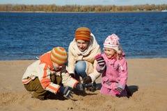 Le garçon et la fille avec la momie jouent la plage sur le côté de fleuve Image libre de droits