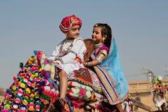 Le garçon et la fille comme une famille royale conduisent au festival de désert Photos stock
