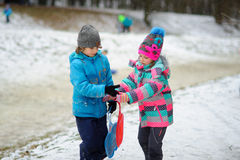 Le garçon et la fille d'un plus jeune âge scolaire pendant l'hiver se garent au sujet de la pente pour des toboggans Photographie stock libre de droits