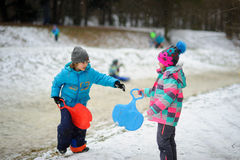 Le garçon et la fille d'un plus jeune âge scolaire pendant l'hiver se garent au sujet de la pente pour des toboggans Photos libres de droits