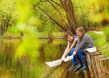 Le garçon et la fille dans des chemises rayées jouent les bateaux de papier Photo stock