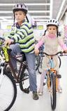 Le garçon et la fille dans les casques s'asseyent sur des bicyclettes Image stock