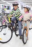 Le garçon et la fille dans les casques s'asseyent sur les bicyclettes lumineuses Photos libres de droits