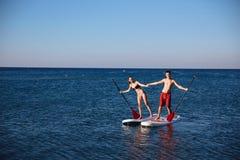 Le garçon et la fille de bonheur sur la petite gorgée surfent la natation à l'océan Mode de vie de concept, sport, amour Image libre de droits
