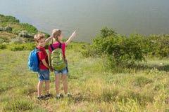 Le garçon et la fille de l'adolescence avec des sacs à dos sur le dos vont sur une hausse, voyage, beau paysage Photographie stock libre de droits