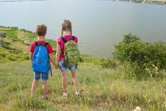 Le garçon et la fille de l'adolescence avec des sacs à dos sur le dos vont sur une hausse, voyage, beau paysage Images stock