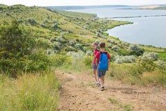 Le garçon et la fille de l'adolescence avec des sacs à dos sur le dos vont sur une hausse, voyage, beau paysage Image libre de droits