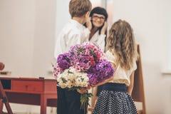 Le garçon et la fille donnent des fleurs comme maître d'école dans le teacher& x27 ; jour de s Photos stock