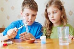 Le garçon et la fille effectuent l'expérience chimique Photo stock