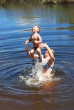 Le garçon et la fille est des piqués baignés, saute dans la rivière. Photos stock