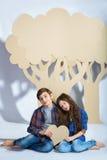 Le garçon et la fille gardent des coeurs pour s'asseoir sous l'arbre de carton Concept d'amour Photographie stock libre de droits