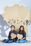 Le garçon et la fille gardent des coeurs pour s'asseoir sous l'arbre de carton Concept d'amour Photos stock