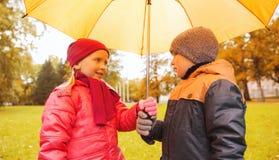 Le garçon et la fille heureux avec le parapluie en automne se garent Photographie stock