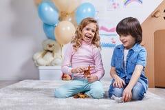 Le garçon et la fille heureux de sourire ont l'amusement chez la pièce des enfants Images libres de droits