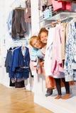 Le garçon et la fille heureux jouent le cache-cache dans des vêtements Photo libre de droits