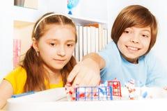 Le garçon et la fille jouant le hockey sur glace ajournent le jeu de société Photographie stock