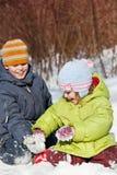Le garçon et la fille jouent se reposer dans la neige en hiver Images libres de droits