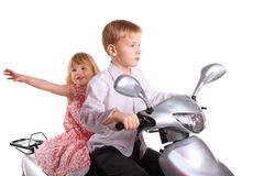 Le garçon et la fille joyeuse s'assied sur la moto Photo stock