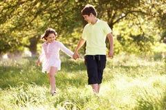 Le garçon et la fille marchant par l'été mettent en place ensemble Images libres de droits