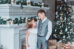 Le garçon et la fille ont habillé d'une manière élégante la position dans une salle lumineuse par la cheminée Arbre de Noël à l'a photographie stock libre de droits