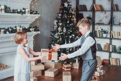 Le garçon et la fille ont habillé d'une manière élégante la position dans une salle lumineuse par la cheminée Arbre de Noël à l'a image stock