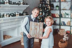 Le garçon et la fille ont habillé d'une manière élégante la position dans une salle lumineuse par la cheminée Arbre de Noël à l'a photos libres de droits