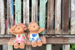 Le garçon et la fille plâtrent des poupées se reposant sur les oscillations, fond en bois Images stock
