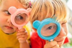 Le garçon et la fille regardent dans une loupe dans la perspective du jardin Enseignement à domicile photo libre de droits