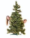 Le garçon et la fille regardent de dessous l'arbre de Noël Image stock
