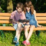 Le garçon et la fille s'asseyent sur un banc en parc, regardant photos libres de droits