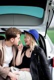 Le garçon et la fille s'asseyent sur un tronc de voiture Photographie stock libre de droits