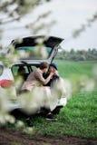 Le garçon et la fille s'asseyent sur un tronc et rire de voiture Photo libre de droits