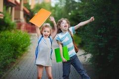 Le garçon et la fille se réjouissent à l'arrêt de l'année universitaire image stock