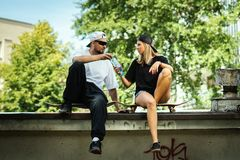 Le garçon et la fille sur des planches à roulettes se donnent l'eau potable  Photo libre de droits