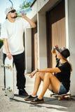 Le garçon et la fille sur des planches à roulettes se donnent l'eau potable  Images libres de droits