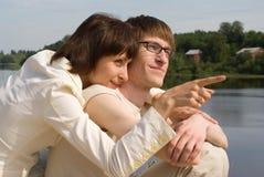 Le garçon et la fille sur le `s de fleuve encaissent Images stock