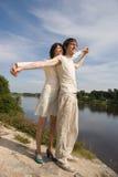 Le garçon et la fille sur le `s de fleuve encaissent Photo stock