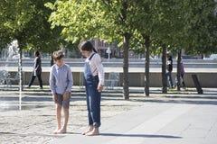 Le garçon et la fille tiennent la fontaine proche aux pieds nus Image stock